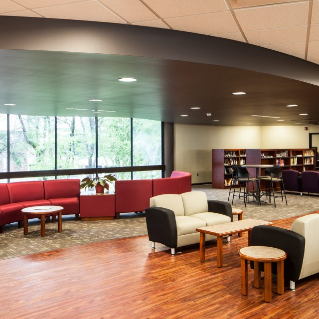 lobby with a red couch and marron, white, and black chairs at Bettendorf High School's Performing Arts Center