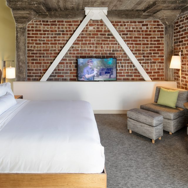 bedroom with two brick walls from the orignal building at the Element Hotel