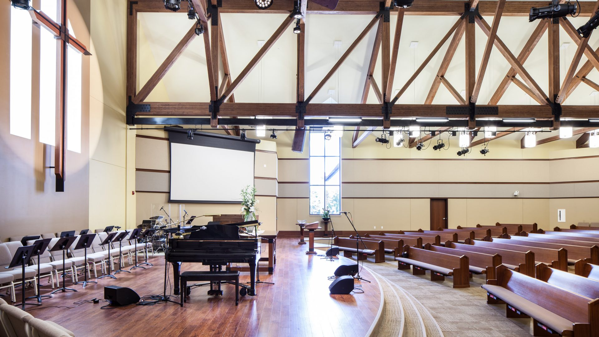 wooden pews and stage with a piano at Geneseo First United Methodist Church