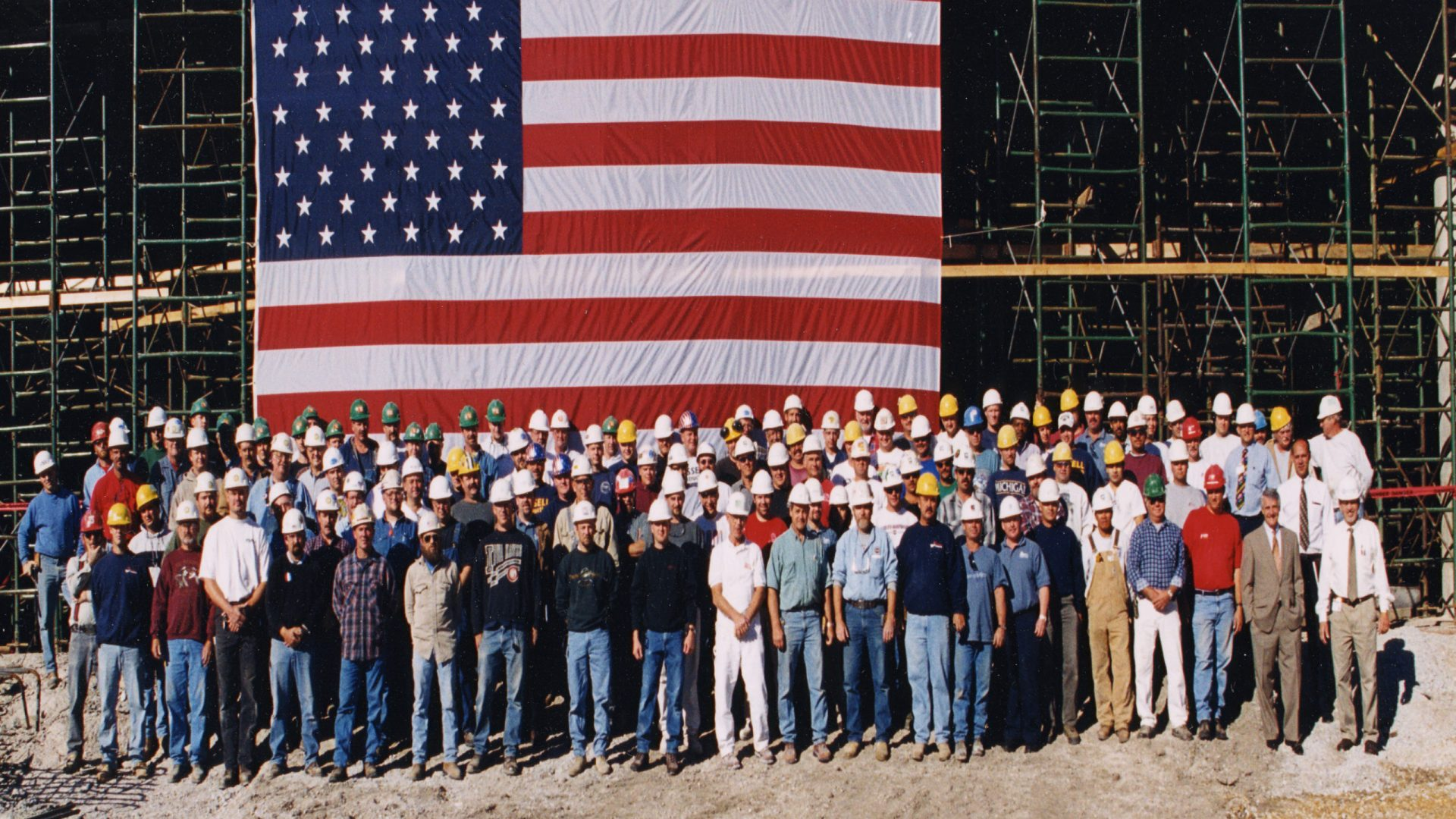 construction workers in hard hats gathered around an American flag at the Genesis East construction site
