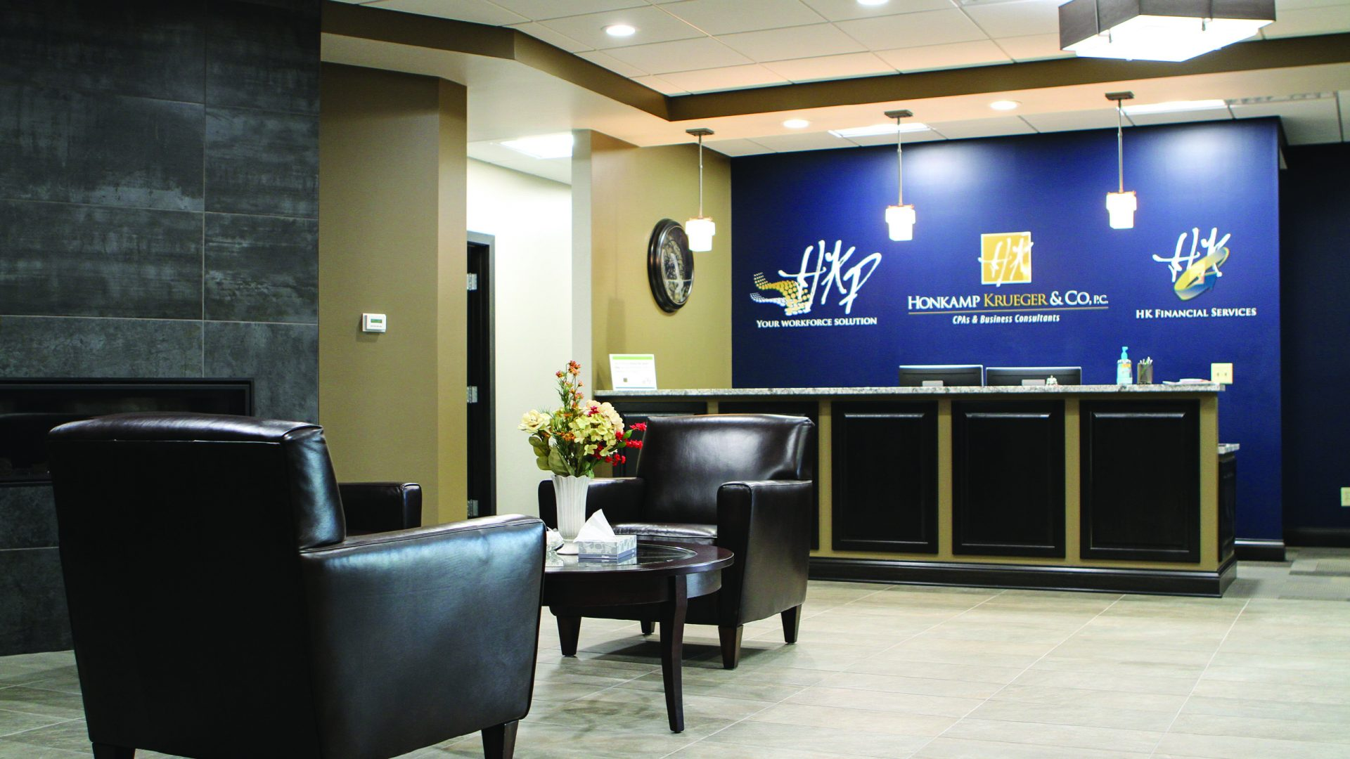 two black chairs in the lobby of Honkamp Krueger and there is a royal blue wall behind the front desk