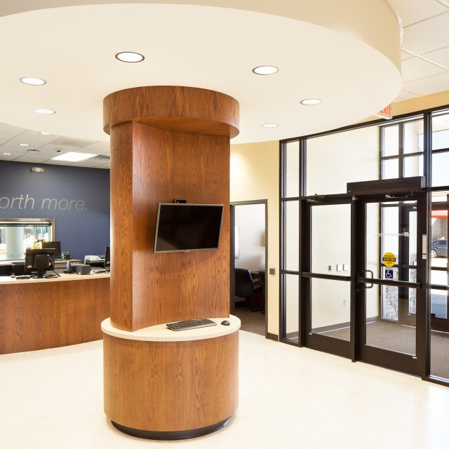 entrance of the IH Mississippi Valley Credit Union Kewanee Branch with a wooden piller in the middle of the room that has a monitor and keyboaord on it