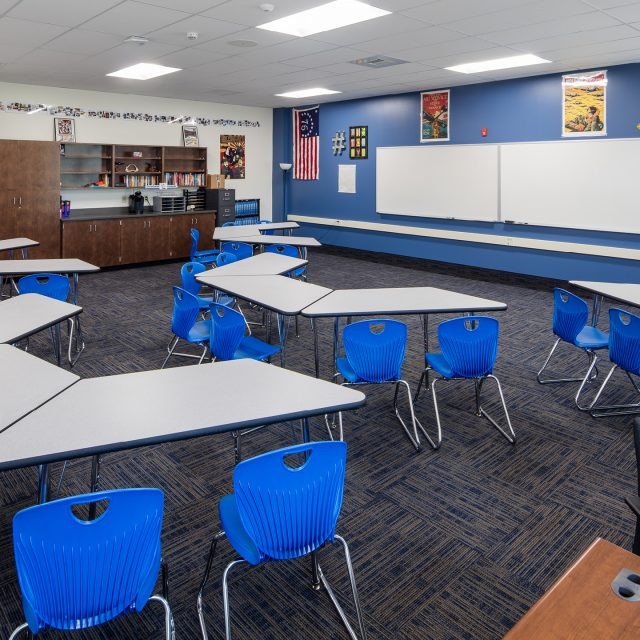 classroom with a blue wall and blue chairs at Quincy High School